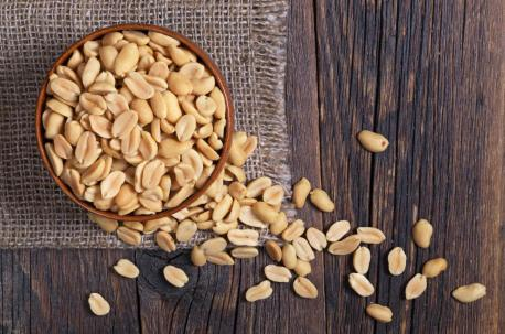 peanuts-in-a-bowl-on-wooden-table-top-down-view